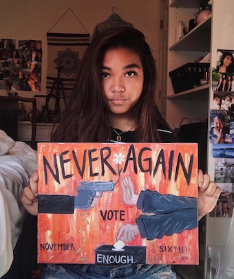 Audrey Hafizian posing with her artwork containing a strong message about gun control. Courtesy of Audrey Hafizian's instagram.